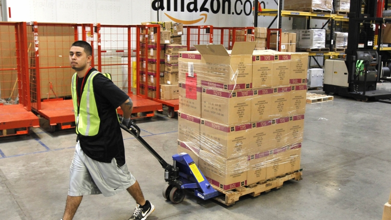 Amazon employee pulling pallet of boxes