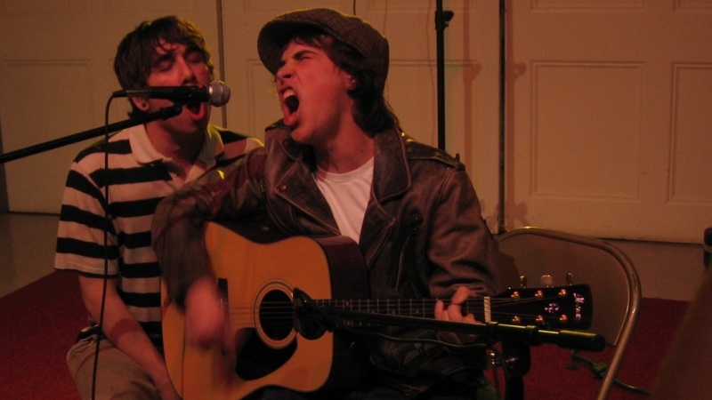 Two men singing into a microphone