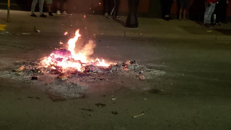 A trash fire smolders near State Street in downtown Madison Saturday night.