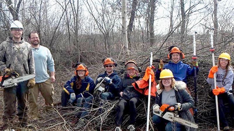 Volunteers pose for a picture after a fall day clearing brush