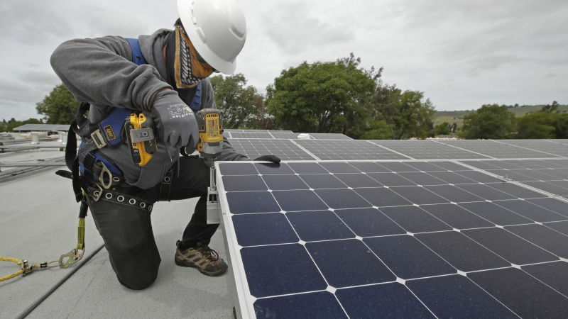 A solar installer works on a panel