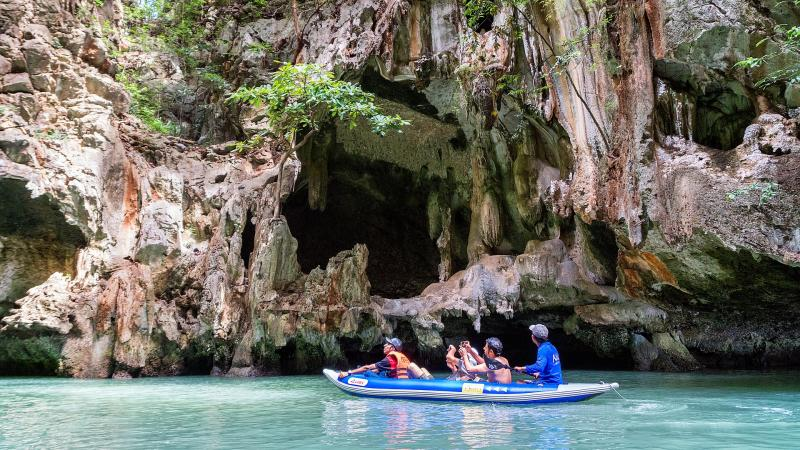 people paddling on water looking at sea caves