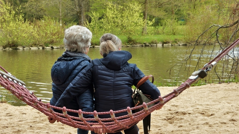 Two older women sitting in hammock outdoors