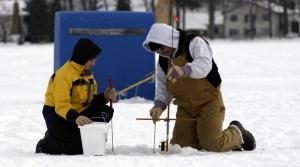 Two people ice fishing on frozen lake.