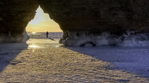 A person is visible in the distance standing between an archway surrounded by frozen surface.
