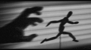 a shadow hand chasing a shadow figure