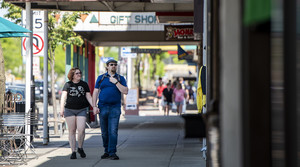 Two people walk on a sidewalk as they examine the exterior of stores on a sunny day.