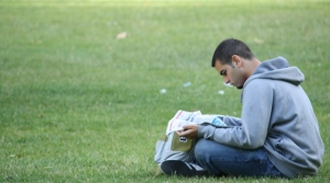 young man reading newspaper on grass