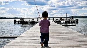 Small boy walking on dock with fishing pole.