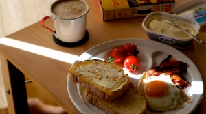 A table with a plate full of eggs and toast, a mug full of hot beverage and a book sit in a sunbeam.