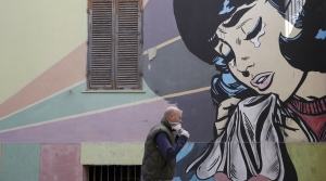A man adjusts his face mask as he walks past a mural of a crying woman