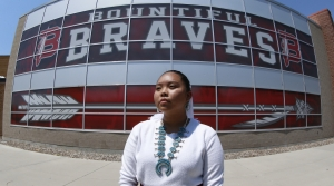 A Navajo student in front of her high school