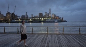 a man wears a face mask as he walks on Pier 45 in Hudson River Park in New York