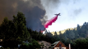An airplane drops retardant on forest fire