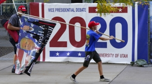 A Trump supporter carries a flag outside the presidential debate venue