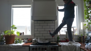 A man stands on his kitchen counter wearing many layers and hovering one boot-covered foot over a steamy stove.