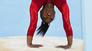 A close-up of Simone Biles' upper body upside down as she performs a flip.