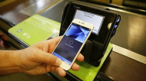 A close-up photo of a person holding their smartphone next to the payment pad of a cash register.