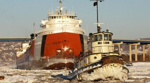 Tug breaking ice in Lake Superior for an ore carrier