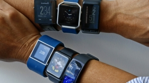 Two wrists display several different kinds of fitness tracker watches with their displays showing the time.