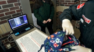 A student gets her bag checked at a metal detector