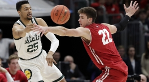 Michigan State's Kenny Goins (25) pass the ball around Wisconsin's Ethan Happ (22) during the first half of an NCAA college basketball game in the semifinals of the Big Ten Conference tournament