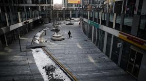 A cleaner walks through a deserted compound of a commercial office building