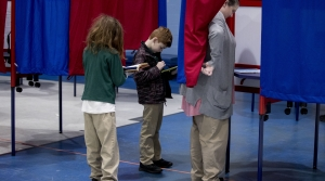 Woman votes in the 2020 New Hampshire presidential primary while her sons wait.