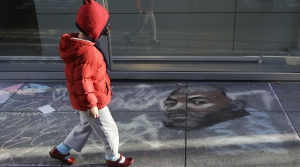 A child walks past a drawing on the sidewalk of Dr. Martin Luther King, Jr. outside of the Museum of the African Diaspora