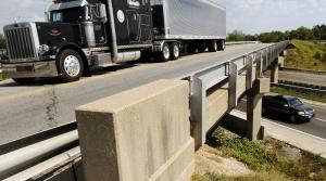 Semi-trailer truck drives on a highway bridge over an interstate