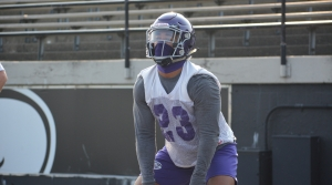 Warhawk football player squatting during practice