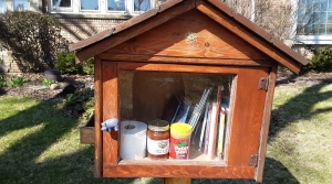 A Little Free Library with books, a roll of toilet paper, jar of spaghetti sauce, jar of peanut butter and chocolate, in Wauwatosa