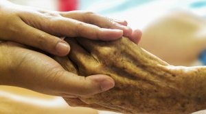 A caregiver holds the hand of a patient