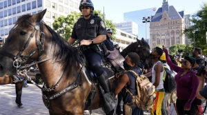 Police officers block protesters at the 2020 Democratic National Convention in Milwaukee.
