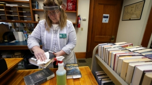 Jane Whitworth, circulation manager for the Bridgton Public Library, wears a face shield while disinfected recently returned books