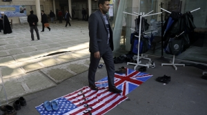 A man walks on U.S. and British flags while leaving a gathering to commemorate the late Iranian Gen. Qassem Soleimani