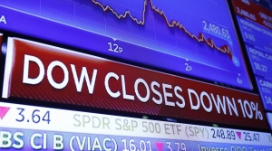 A television screen on the floor of the New York Stock Exchange headlines the day's activity, Thursday, March 12, 2020