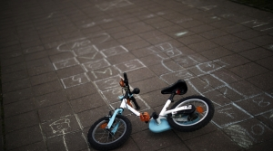 A child bicycle lies next to hopscotches sketched on the ground
