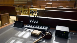 A gavel sits on a desk inside a courtroom