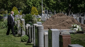 Robert Salerno, a funeral director, wears a mask as he reviews a gravesite