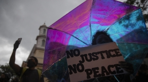 "A woman holds a sign that reads ""No Justice No Peace"" under an umbrella i"