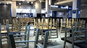 Chairs hang stacked on empty tables at a closed restaurant