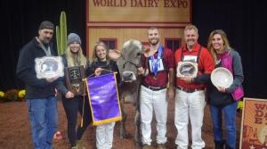 a dairy farmer poses with his family and a cow