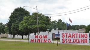 Signs along Charles Street in Oconto, Wis. advertise job openings at LeTourneau Plastics.