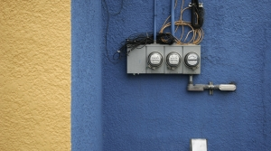 Yellow and blue stucco wall decorated with a scattershot corsage of electric meters, conduit and wiring.