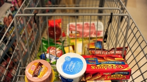 A close-up view of a shopping cart in a grocery store with a few items in the cart.