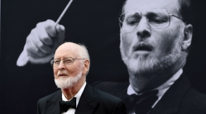 Composer John Williams stands in front of a large picture of himself conducting