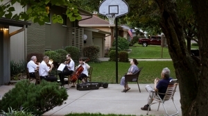 A group of musicians sit together outdoors to play music; two viewers sit nearby, but spaced apart to listen.