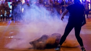 A protester lies in the street underneath teargas