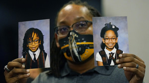 A parent holds up photos of his children, who have sickle cell anemia